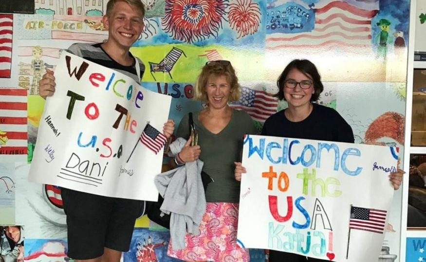 Host mother welcoming two exchange students