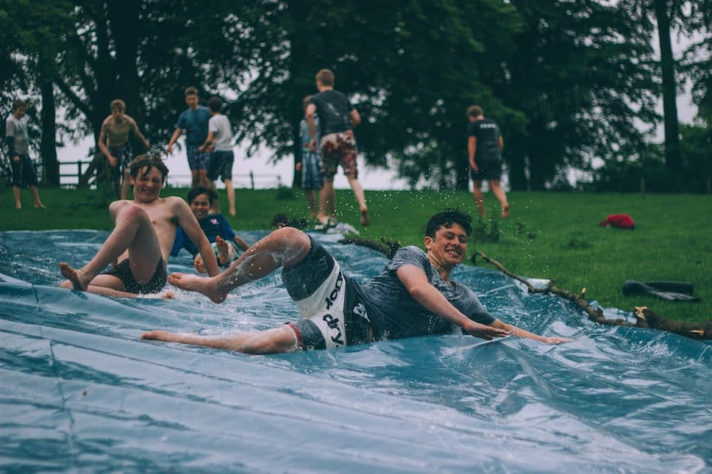exchange students on water slide with host families